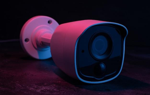 Câmera de segurança na parede escura na luz rosa e azul.