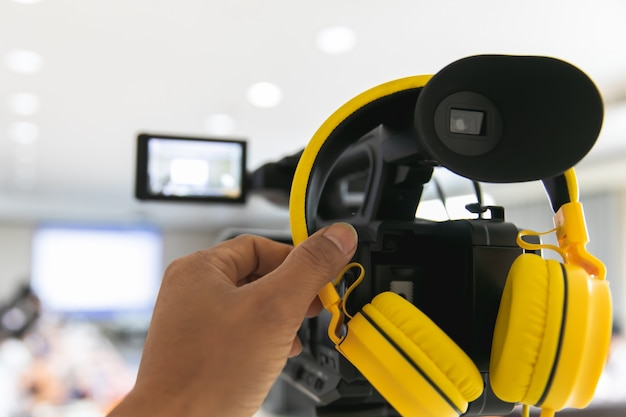 Câmera de vídeo em participantes de gravação de sala de conferências de negócios e fone de ouvido
