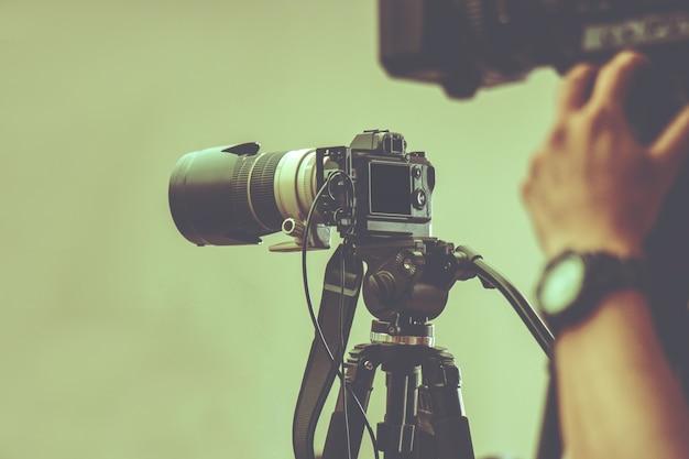 Câmera de vídeo profissional com tripé em espera para fotografar na produção de estúdio