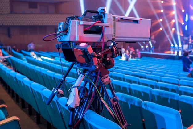 Câmera de vídeo profissional em um tripé com uma tela para eventos e transmissão de tv