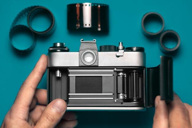 Câmera de vídeo vintage antiga na mão masculina em azul