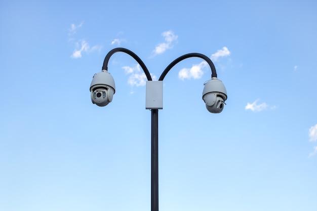 Câmera de vigilância de cctv (circuito fechado de televisão) instalada em parque público em fundo de céu azul para proteção contra crimes, observação de pessoas, controle da observância da ordem pública.