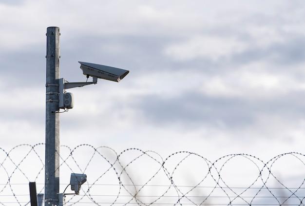 Câmera de vigilância e arame farpado