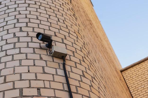 Câmera de vigilância na fachada de um prédio residencial de tijolos. segurança. controle sobre a observância da lei e da ordem.