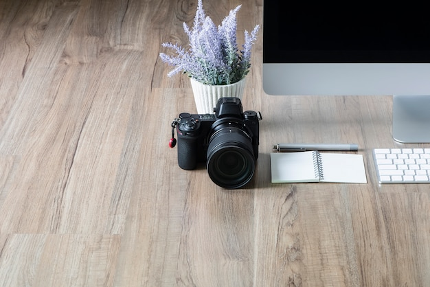 Câmera digital, computador desktop e planta de casa no fundo da mesa de madeira