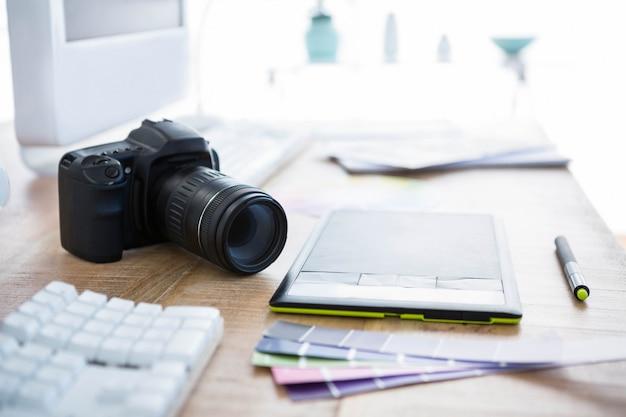 Câmera digital e amostras de cores em uma mesa de escritório