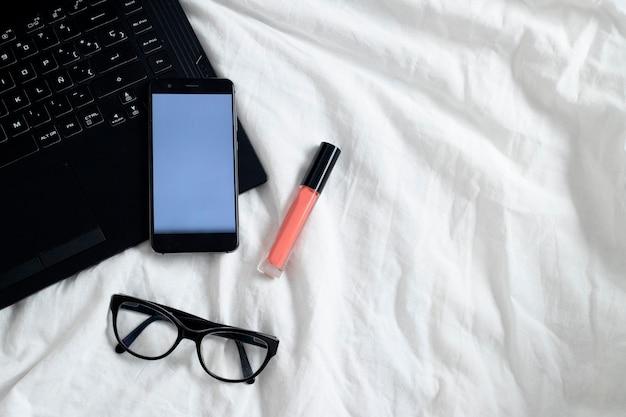 Câmera digital e maquiagem nos lençóis da cama