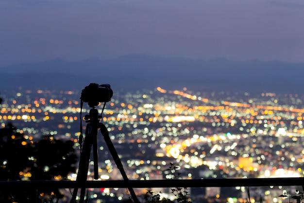 Câmera digital no tripé, tendo a visão noturna da cidade