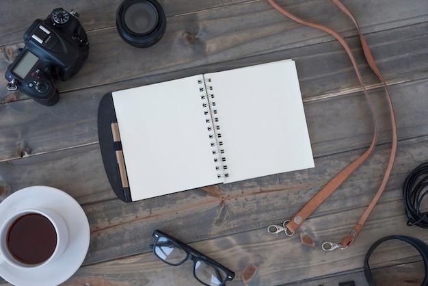 Câmera digital profissional; xícara de café; bloco de notas espiral em branco; caneta; óculos e cabo na mesa de madeira