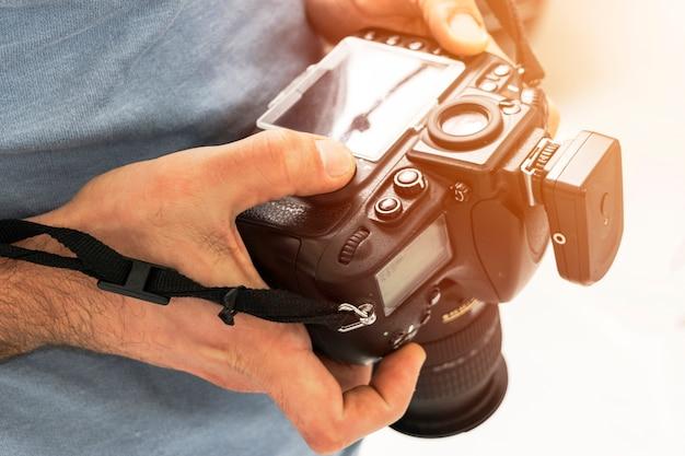 Câmera digital reflex de lente única em mãos masculinas. mãos masculinas segurando o close-up da câmera