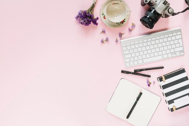 Câmera digital; teclado; canetas de feltro e artigos de papelaria no fundo rosa