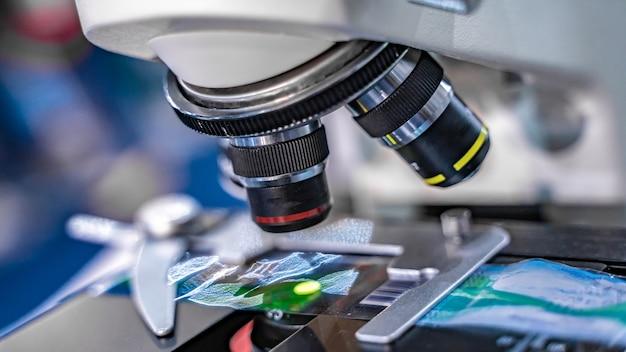 Câmera do microscópio de digitas que indica o vídeo em um monitor na corrediça de vidro da microscopia