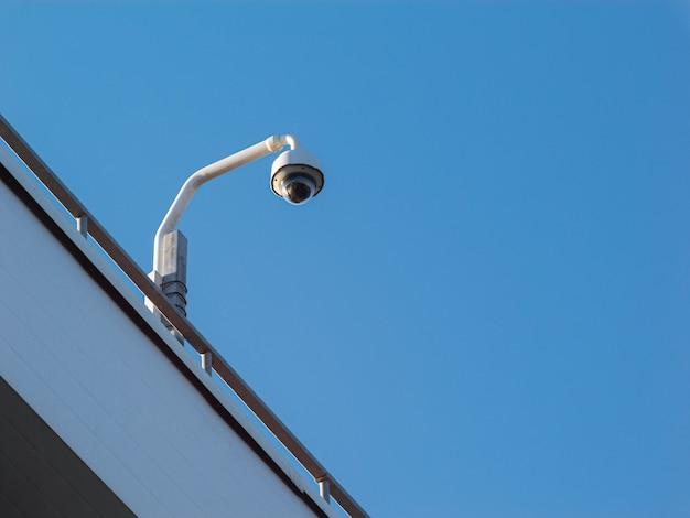Câmera dome na fachada do prédio contra o céu azul