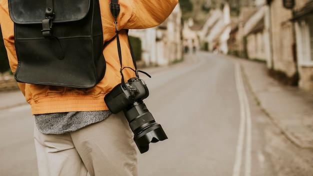 Câmera dslr com alça pendurada no ombro do fotógrafo