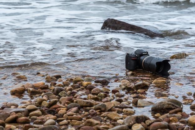 Câmera dslr na praia molhada da onda do mar de água