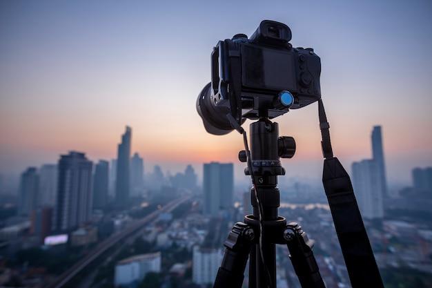 Câmera dslr profissional sem espelho em um tripé, tirando fotos dos belos momentos durante o pôr do sol, nascer do sol.
