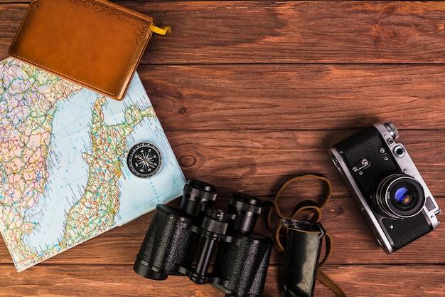 Câmera e binóculo com bússola no mapa e diário