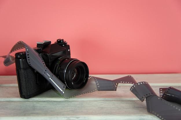 Câmera e filme fotográfico em uma superfície branca