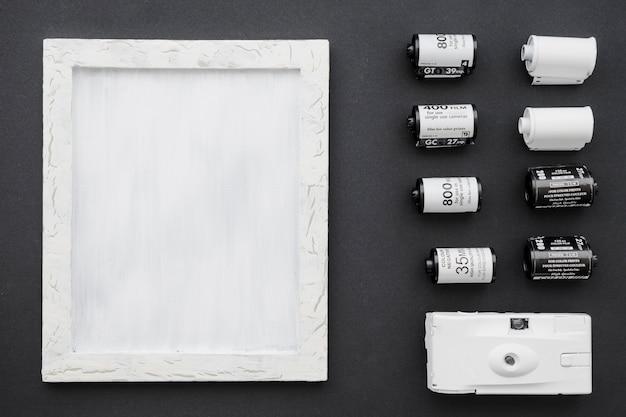 Câmera e filme perto de moldura branca