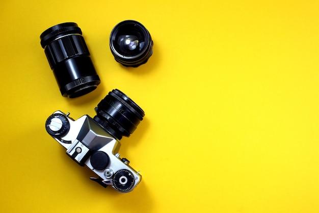 Câmera e lentes retrô encontram-se sobre um fundo amarelo.