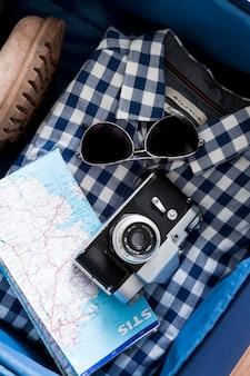 Câmera e mapa na camisa na mala