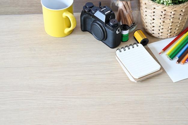 Câmera e materiais de escritório criativos do espaço de trabalho na mesa de madeira.