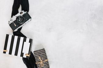 Câmera e pano perto de notebook e presente