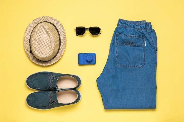 Câmera e roupas masculinas de verão em uma superfície amarela. espaço para o texto. postura plana.