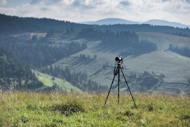 Câmera e tripé ajustados contra a paisagem montanhosa
