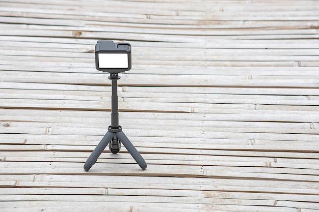Câmera e vídeo com pequeno carrinho preto sobre um piso de bambu.