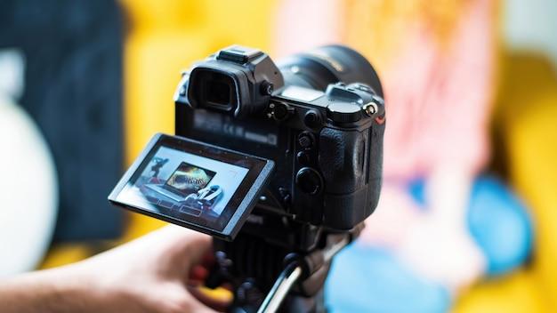 Câmera em um tripé filmando uma mesa com coisas do criador de conteúdo. laptop, microfone e fones de ouvido. trabalhando em casa