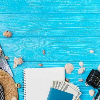 Câmera entre conchas e dinheiro com o bloco de notas