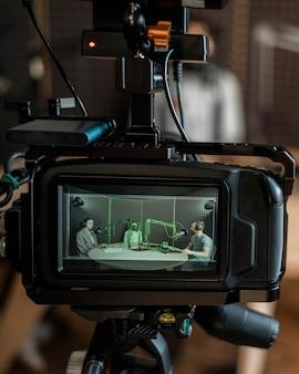 Câmera filmando pessoas na rádio