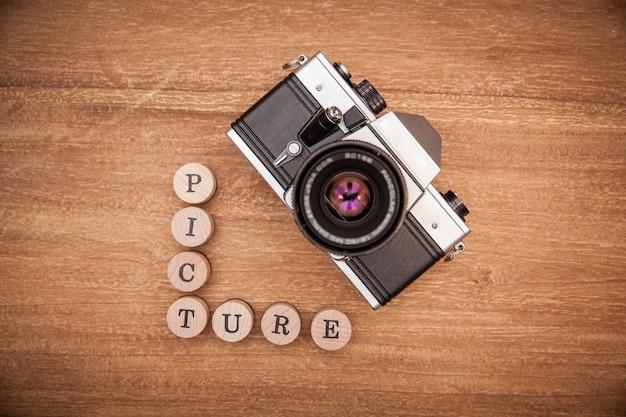 Câmera fotográfica antiga com lente na mesa de madeira.