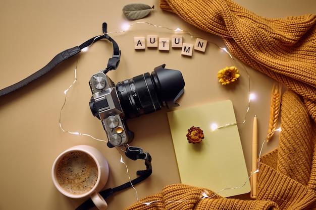 Câmera fotográfica, café e suéter de malha laranja
