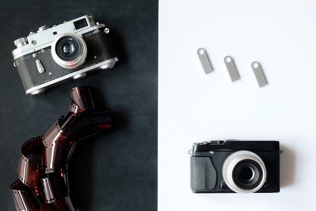 Câmera fotográfica de filme retro de 35 mm com filme em fundo preto e câmera digital moderna e flash drives de prata sobre fundo branco