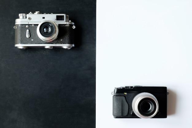Câmera fotográfica de filme retro de 35 mm em fundo preto e câmera digital moderna em fundo branco