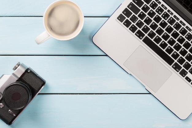 Câmera fotográfica retrô, computador laptop moderno e xícara de café cappuccino