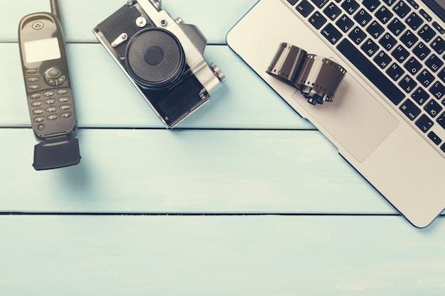 Câmera fotográfica retrô, laptop moderno, telefone celular móvel retrô e filme