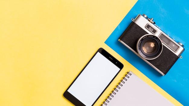 Câmera fotográfica vintage e smartphone em fundo colorido