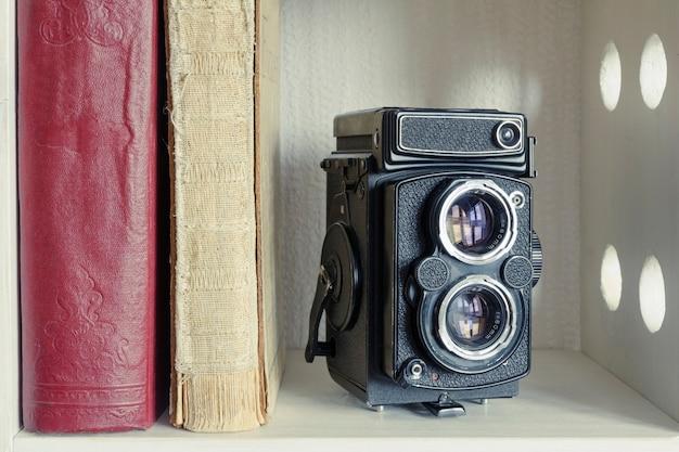 Câmera fotográfica vintage tlr com livros antigos na prateleira branca