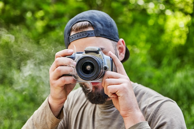 Câmera fuma nas mãos de jovem fotógrafo barbudo de boné de beisebol, viseira voltada para trás, que tira foto na natureza.