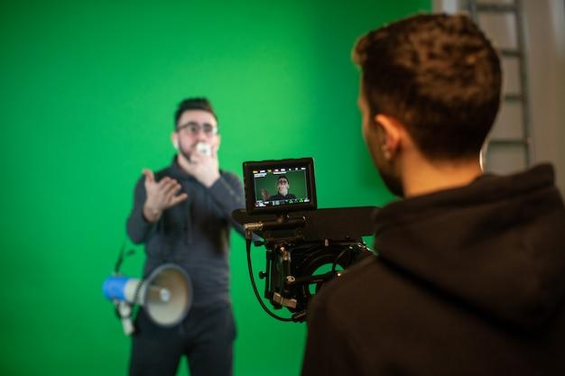 Câmera homem filma cara com alto-falante na câmera
