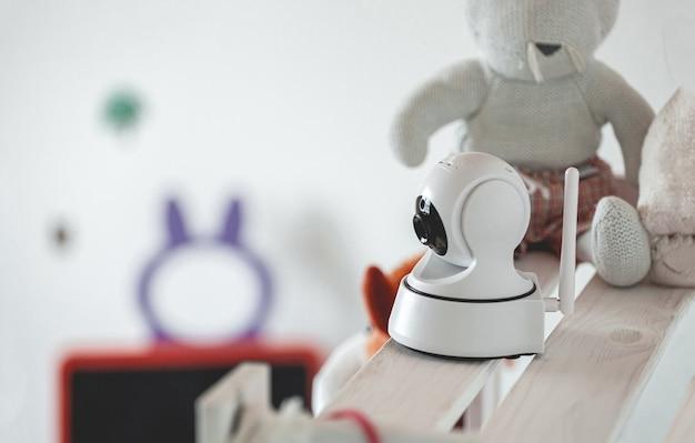 Câmera ip na prateleira com brinquedos, servindo como monitor de bebê
