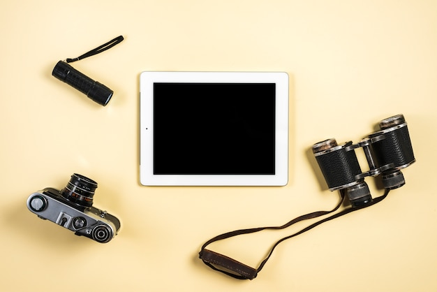 Câmera; lanterna; tablet binocular e digital sobre fundo bege