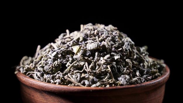 Câmera lenta: folhas de chá caem em uma pilha de um chá verde - tiro macro.
