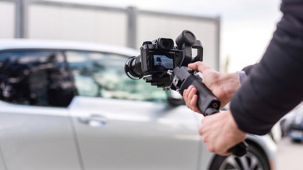 Camera man com estabilizador de tiro estacionado em bmw i3