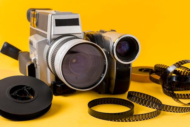 Câmera moderna; carretel de filme e tiras de filme em fundo amarelo