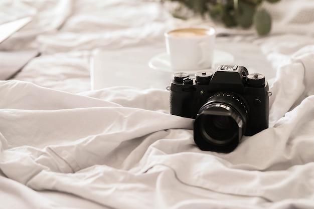 Câmera na cama e xícara de café