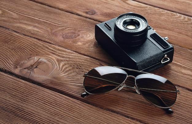Câmera, óculos de sol. acessórios de estrada em uma mesa de madeira.